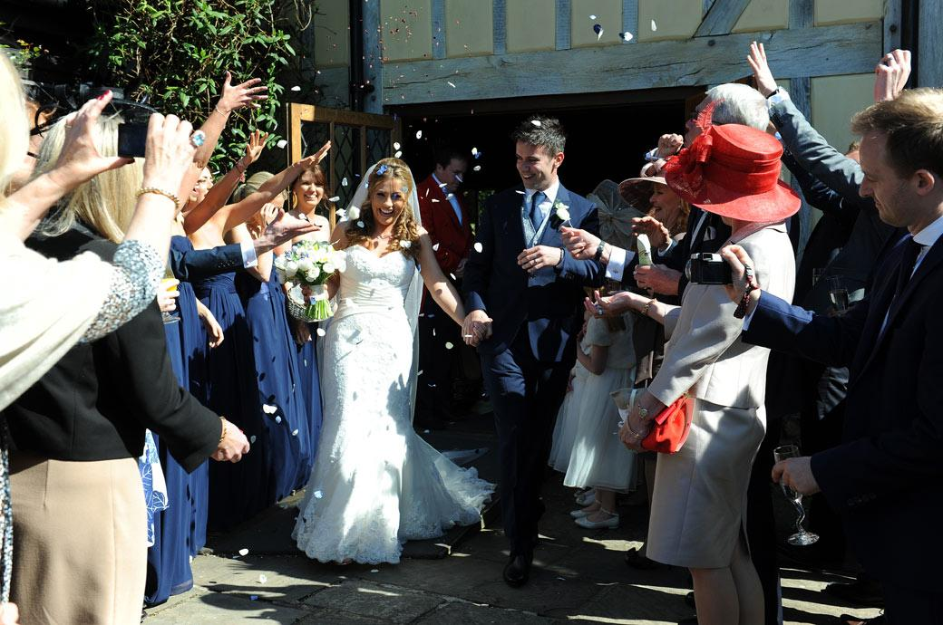 Lots of confetti fun for the happy newlyweds as they walk down the patio in this Surrey wedding photograph taken at Cain Manor in the village of Churt
