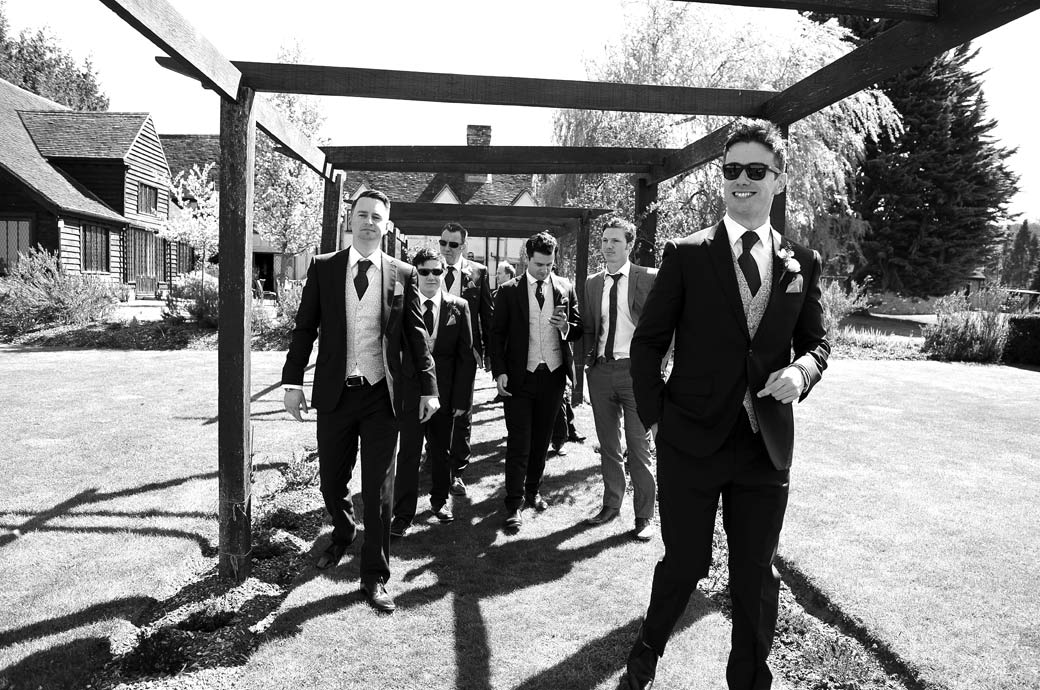 Smiling handsome Groom in sunglasses leading the way down the garden at Surrey wedding venue Cain Manor in Churt for some pre wedding photos before the Bride arrives