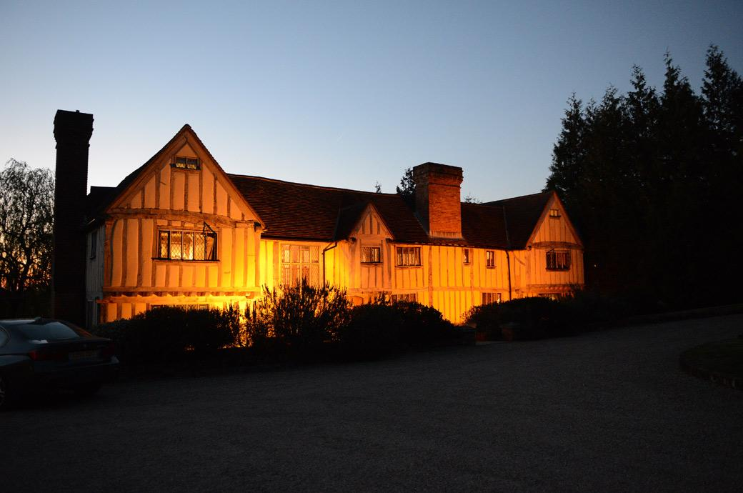 A wedding photograph of the 16th century country house Cain Manor Surrey captured in the evening while everyone is celebrating in the Music Room on the dancefloor