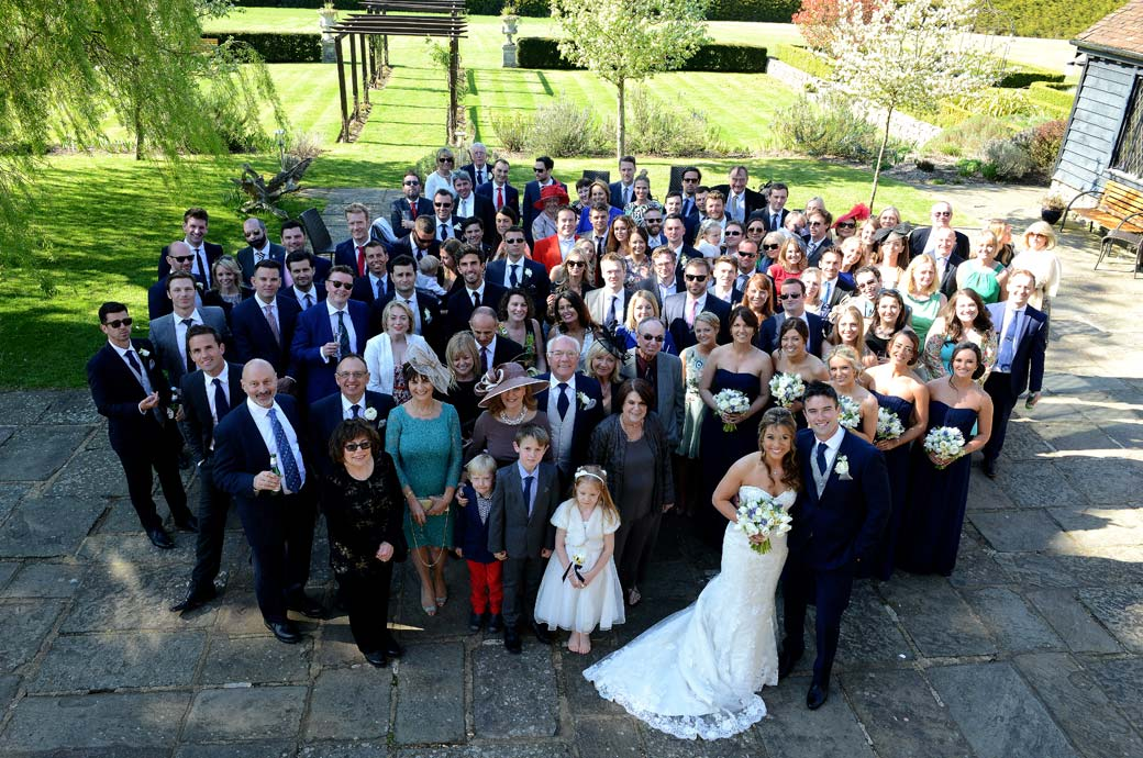 Everyone in this group wedding photograph out in the courtyard at Cain Manor captured by Surrey Lane wedding photographers