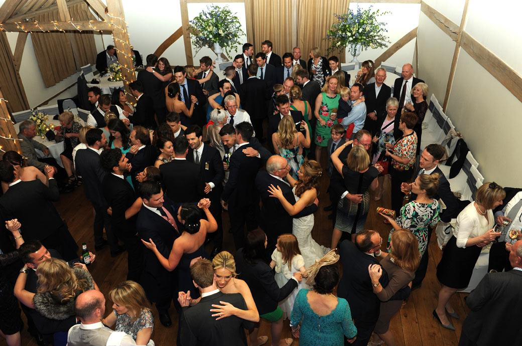 A packed dancefloor in this wedding photo taken from the minstrel gallery in the Music Room at the lovely Cain Manor in Churt a charming and beautiful Surrey wedding venue