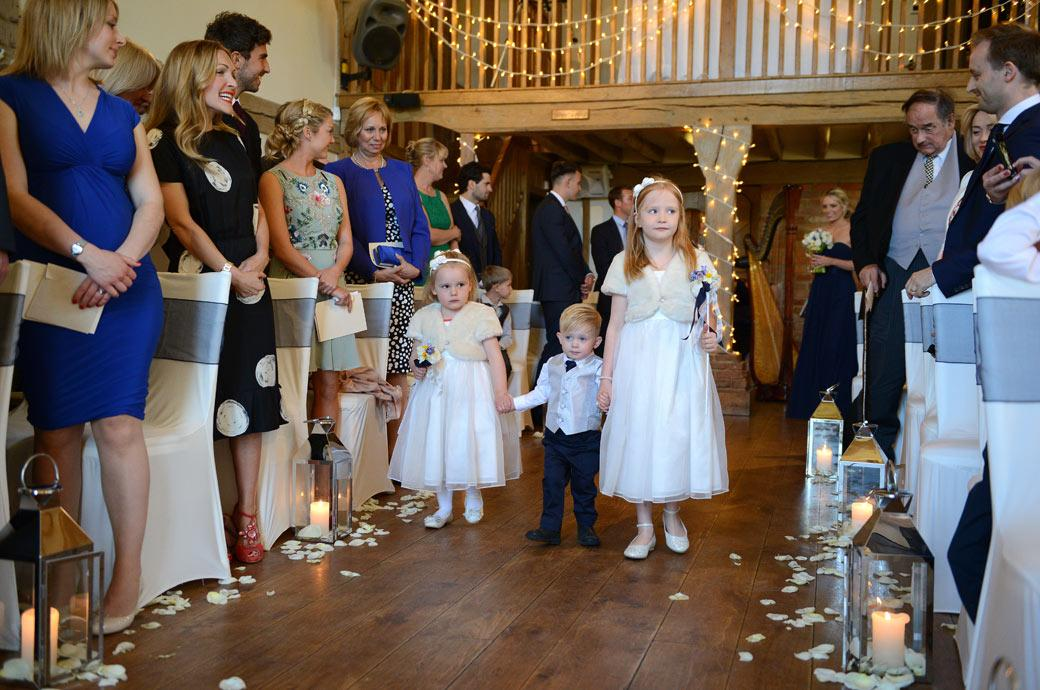 Cute wedding photograph of rather shy and overwhelmed flowers girls and a page boy captured as they walk down the aisle at Surrey wedding venue Cain Manor