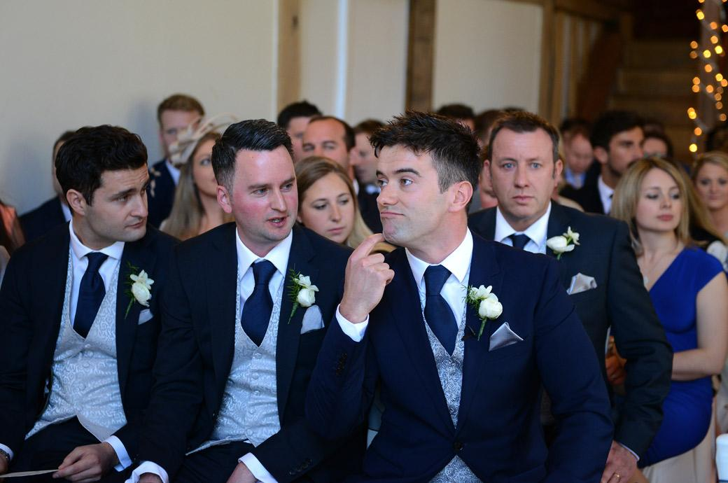 Fun wedding picture of the Groom rubbing his chin as he answers his best men as they awaits the arrival of the Bride at Surrey wedding venue Cain Manor in the Music Room