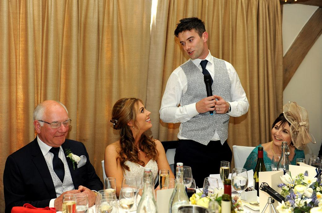 The Groom entertains the top table at the wedding breakfast during the speeches captured in this wedding picture from Cain Manor surrey in the Music Room