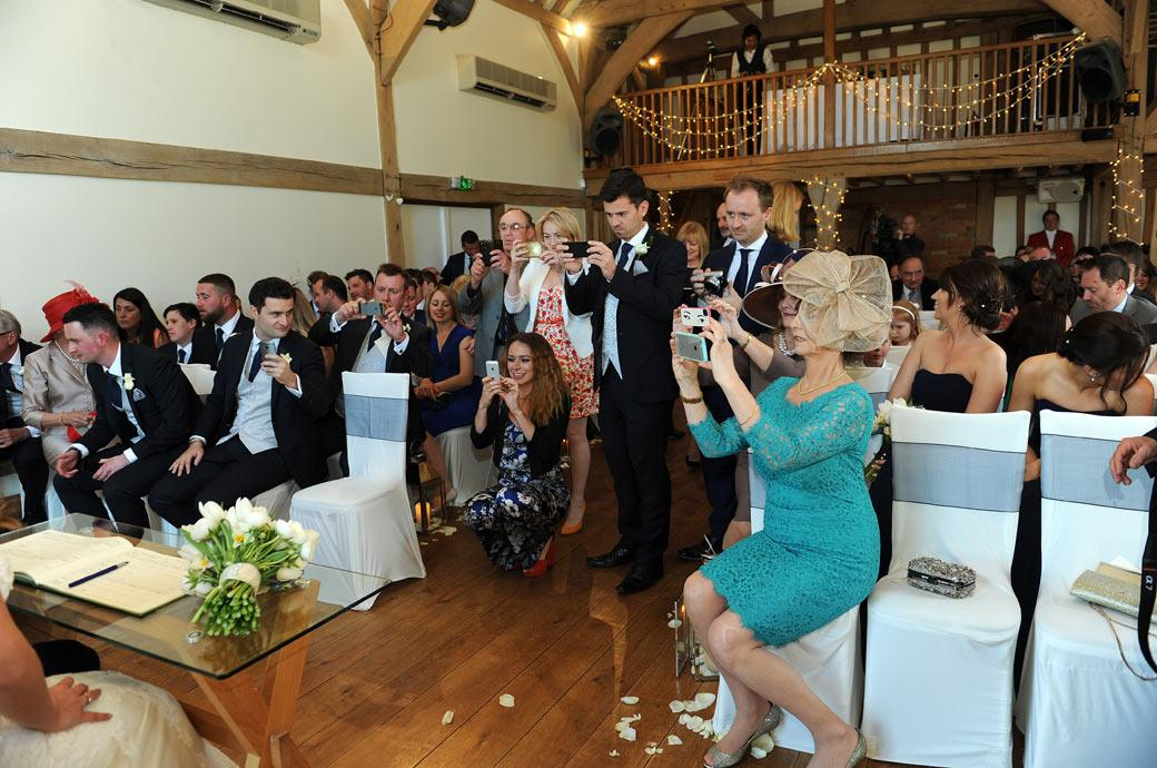 Camera and phones to the ready as guests take wedding photos of the newlyweds in the lovely Music Room at Cain Manor in Churt a luxurious Surrey wedding venue
