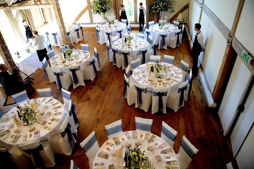 A wedding picture from the minstrel gallery at Surrey wedding venue Cain Manor of the Music Room prepared for the wedding breakfast and awaiting the arrival of the guests