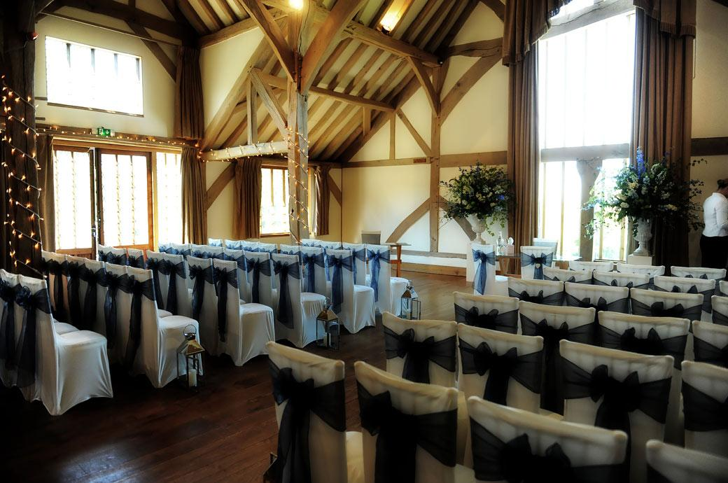 The lovely oak beamed Music Room with its cathedral windows and white walls set out ready for the start of the marriage service in this Cain Manor Surrey wedding photograph