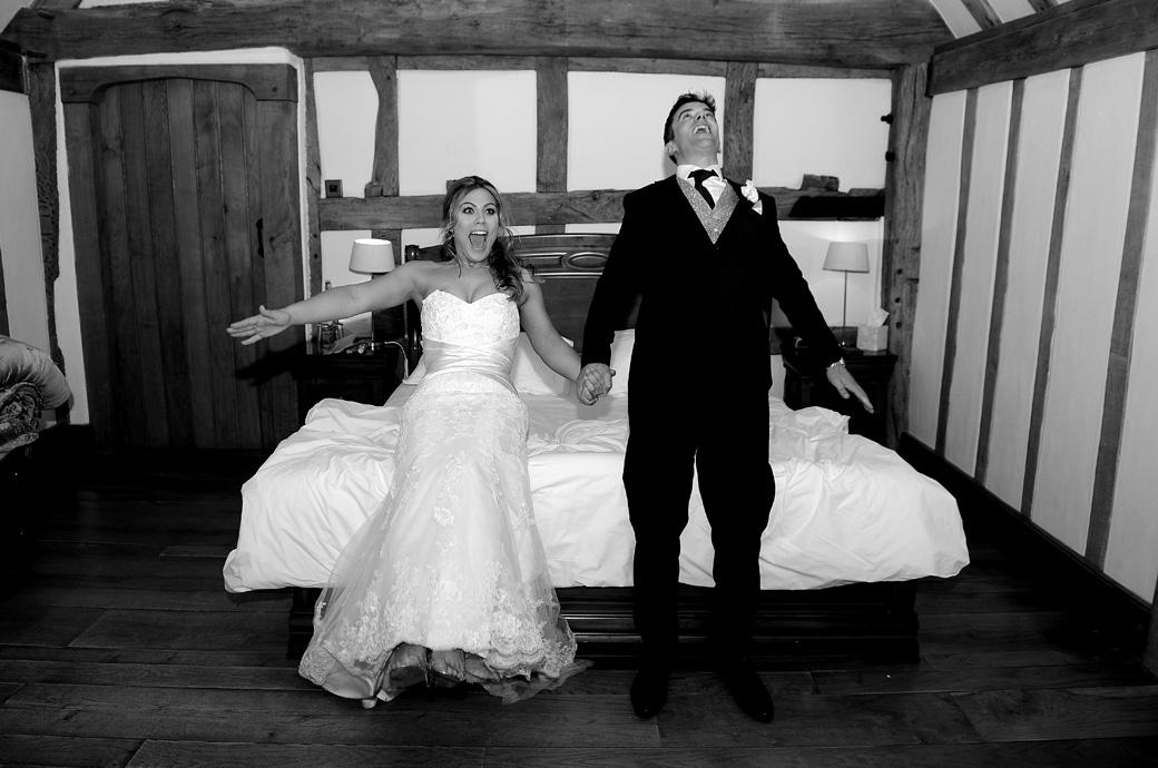 Time for the Bride and Groom to do their party act of falling backwards on a bed captured in this fun wedding photo taken at Cain Manor in Churt Surrey
