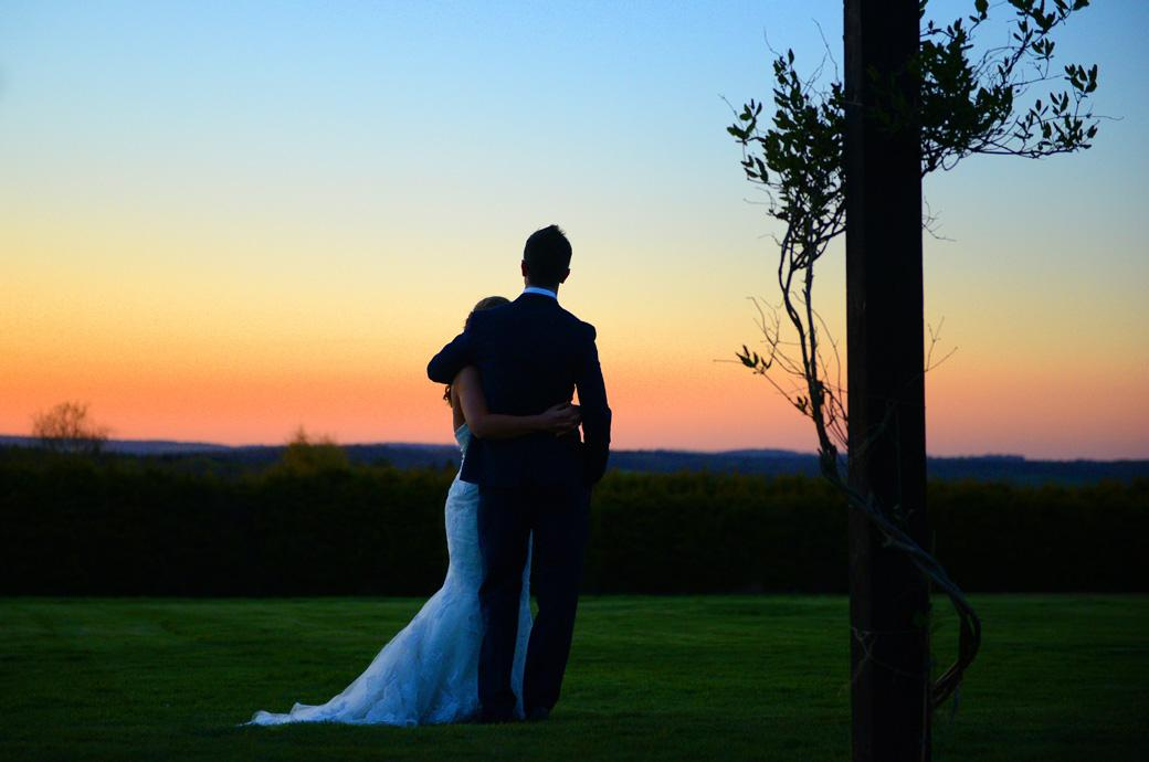 Bride and Groom standing together watching the beautiful sun set in this romantic wedding photo captured at Cain Manor, Churt by a Surrey Lane wedding photographer
