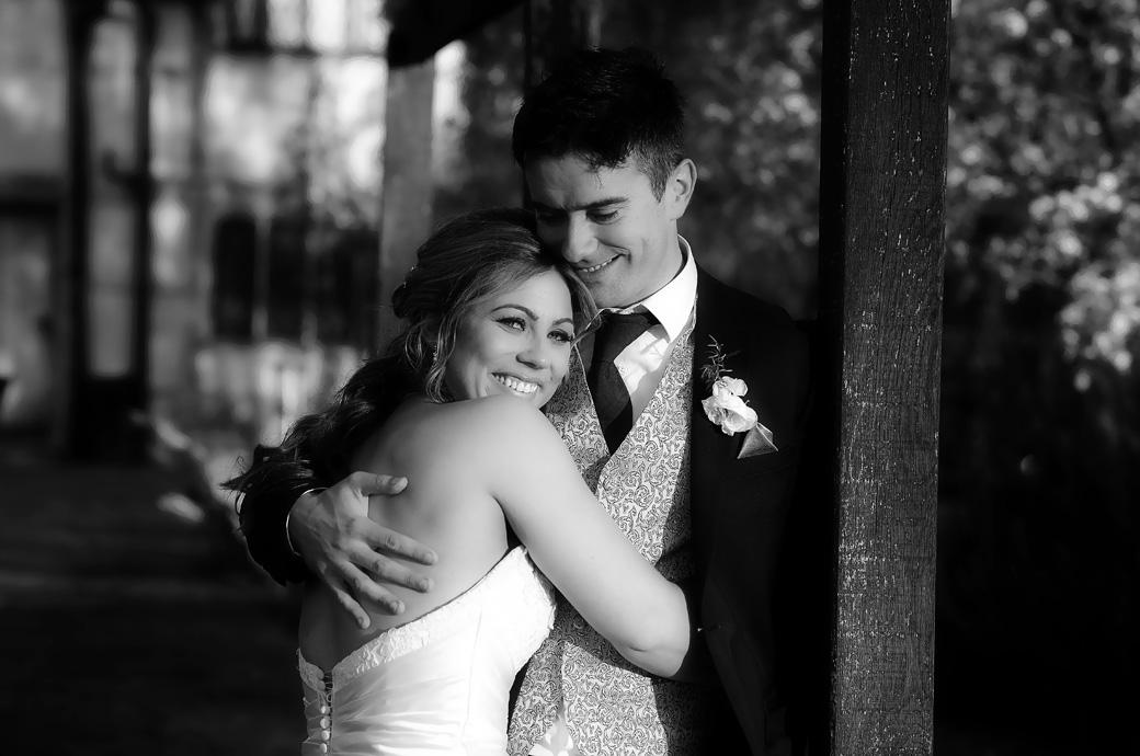 Romantic wedding photograph of a very happy Bride being cuddled by her new husband in the lovely grounds at Surrey wedding venue Cain Manor in the village of Churt