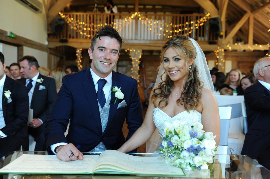 Handsome happy and smiling newlywed couple signing the marriage register in the Music Room in this relaxed wedding photograph at Cain Manor in Churt Surrey