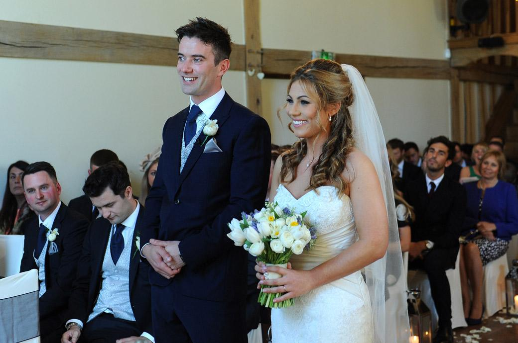Happy smiling Bride and Groom captured in this wedding photo as they listen to the registrar complete the marriage ceremony at Surrey wedding venue Cain Manor
