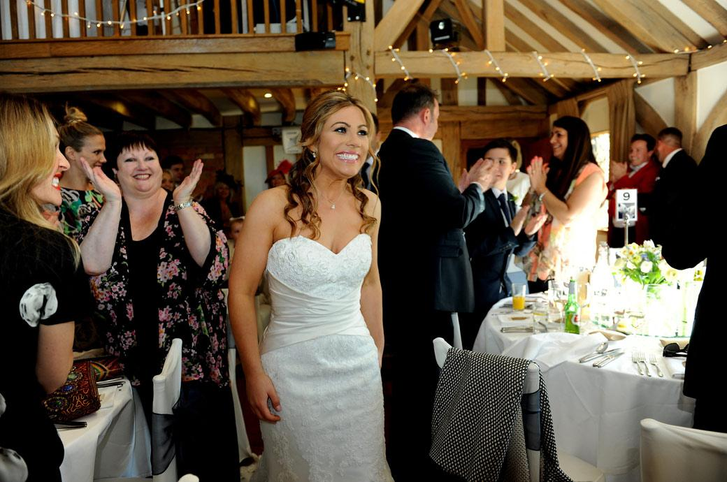 A beaming Bride is applauded as she walks past the guests ready to start the wedding breakfast captured in this wedding photo from Cain Manor Surrey in the Music Room