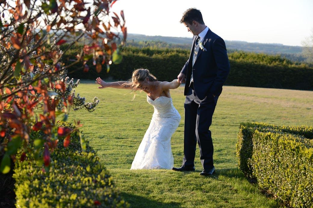 Groom holds onto the hand of his Bride as she tries to climb  the lawn in her high heels in this Cain Manor wedding picture captured by Surrey Lane wedding photographers
