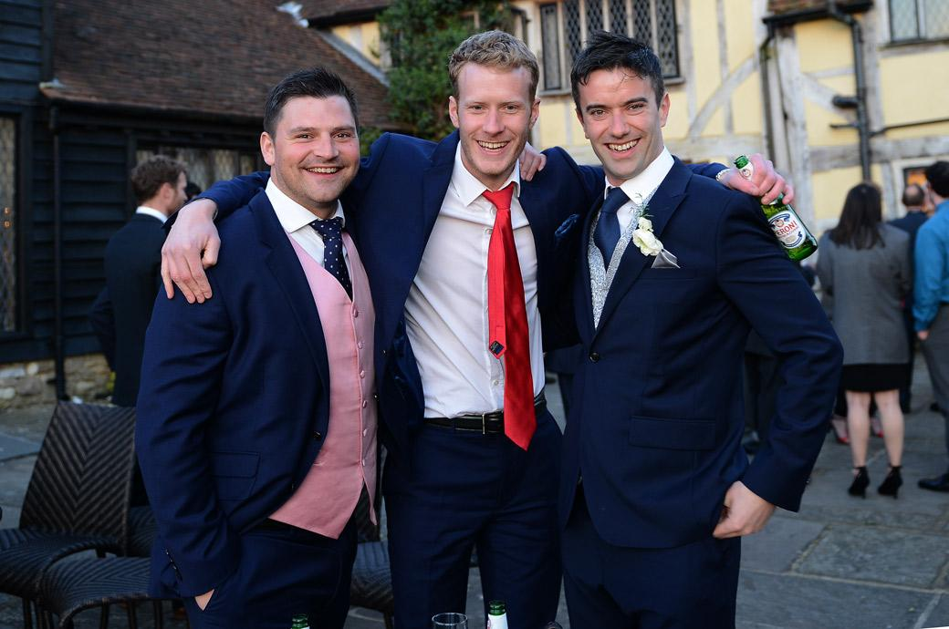 A relaxed Groom enjoying himself with a couple of friends in the courtyard in this wedding photograph from Cain Manor a 16th century country house wedding venue in Surrey