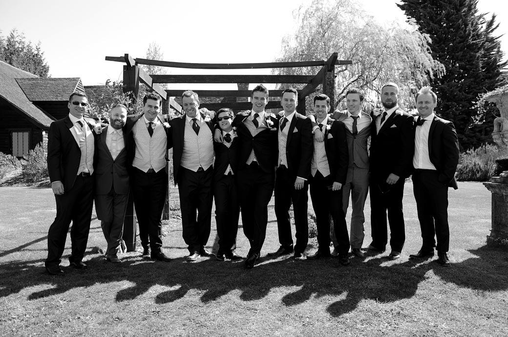 The Groom still single posing with all his men in this pre wedding photograph taken in the grounds of Surrey wedding venue Cain Manor in Churt village