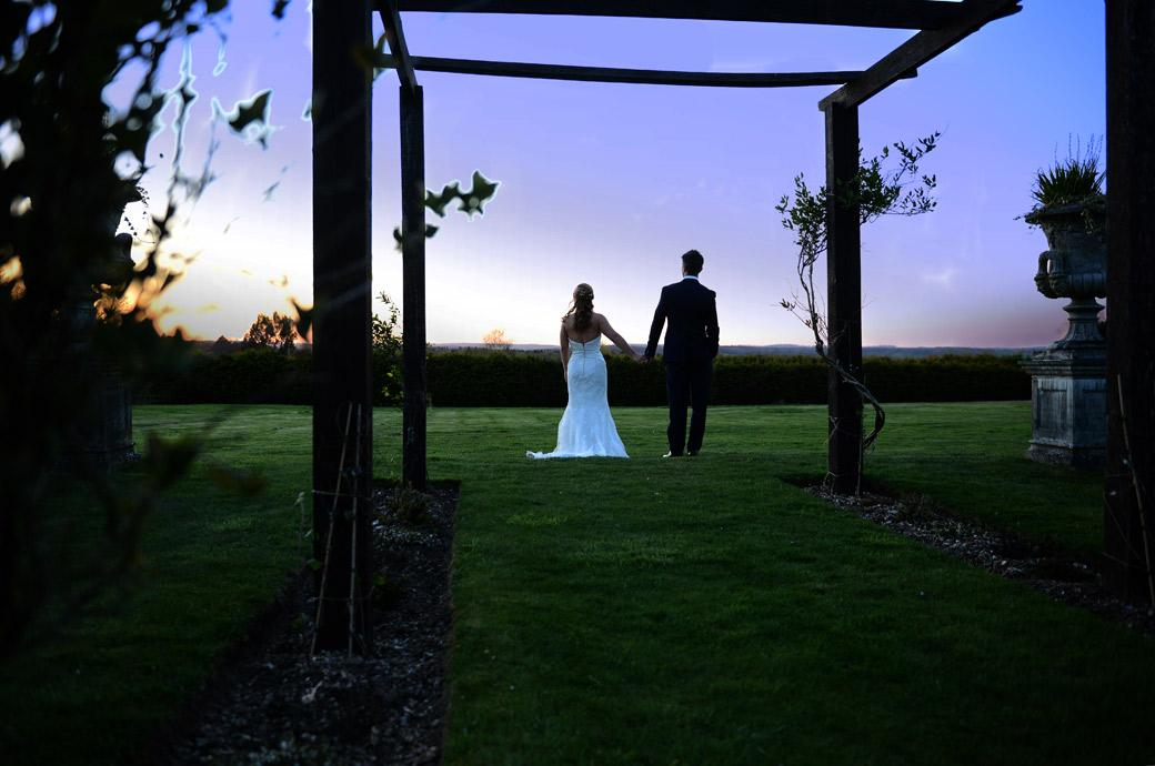 Romantic wedding picture of the newlyweds walking hand in hand to watch the sunset on their marriage day at Cain Manor a Surrey wedding venue that exudes charm and tranquilty
