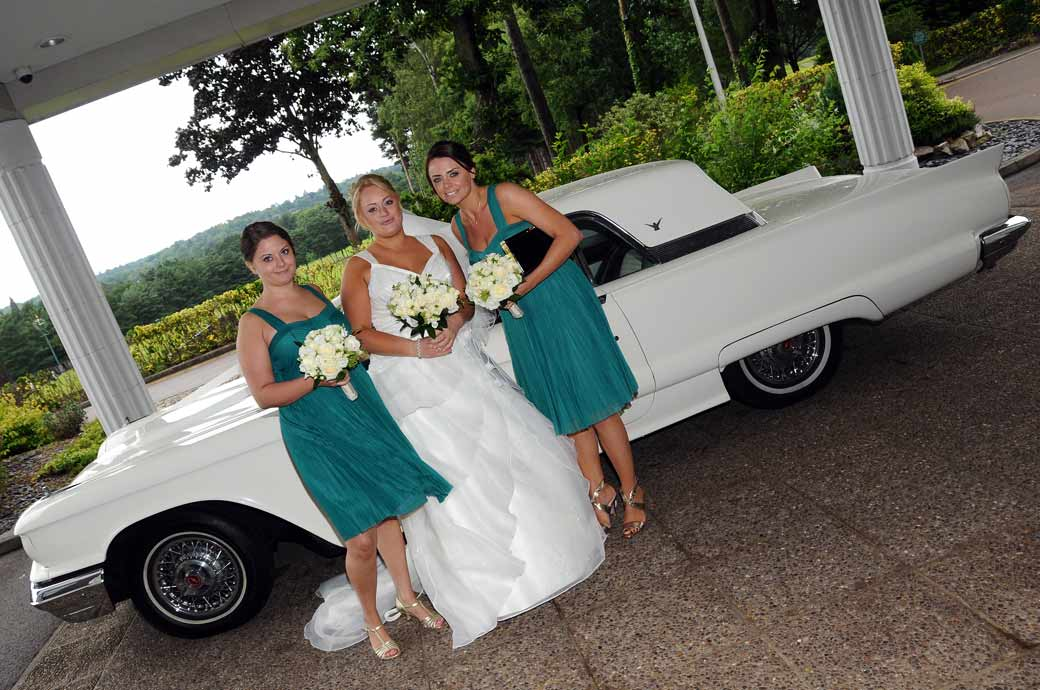 Voluptuous Bride and Bridesmaids wedding photo posing at the entrance of Camberley Heath Golf Club Surrey with a Classic Thunderbird wedding car
