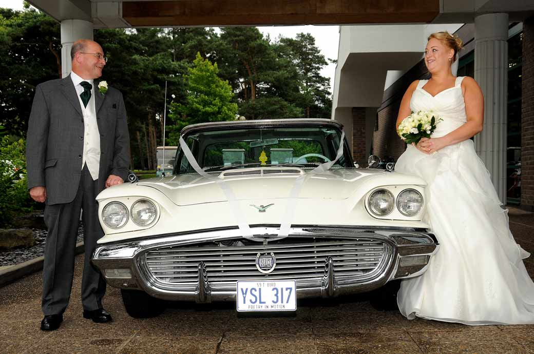 Lovely Father and Bride wedding photograph posing with their fabulous vintage Thunderbird wedding car at the scenic Camberley Heath Golf Club Surrey