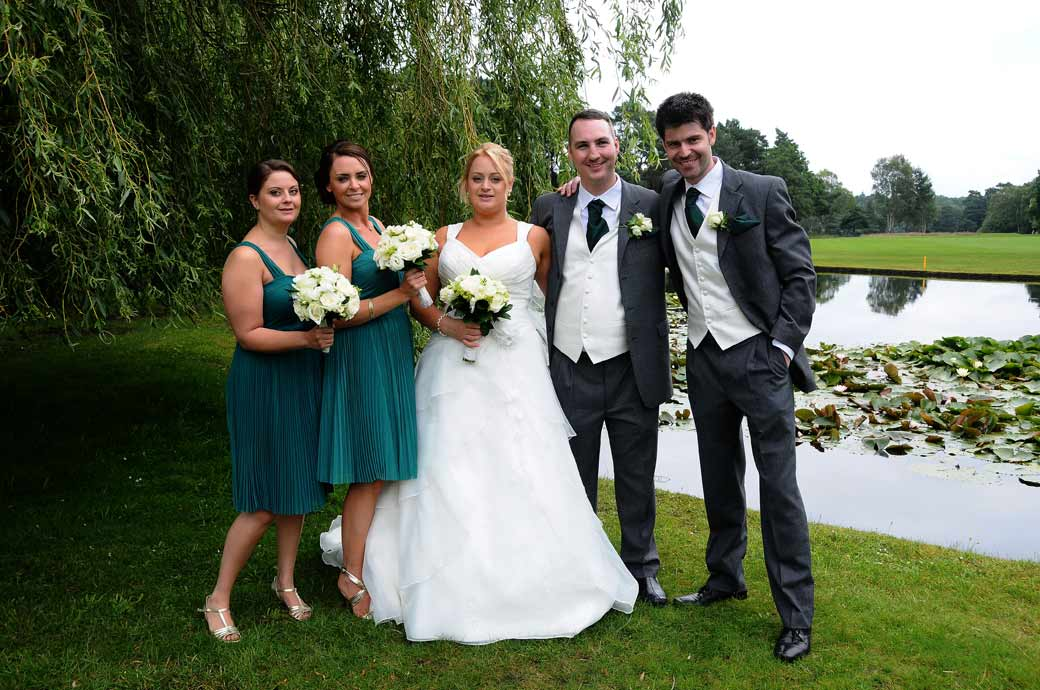 Happy couple with best friends wedding photograph taken by the lake at Camberley Heath Golf Club wedding venue by Surrey Lane wedding photography
