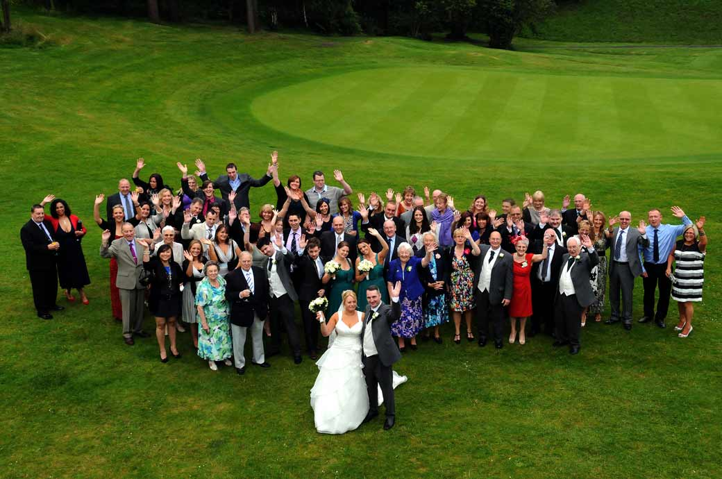 A jolly wedding photograph of the bride and groom and  guests waving with the beautiful green backdrop taken in Surrey Camberley Heath Golf Club