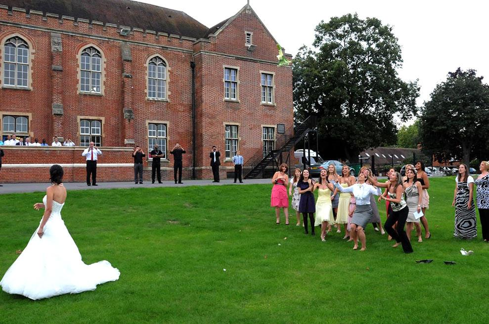 Bride throws her bouquet to the excited and expectant ladies at Surrey wedding venue Carew Manor out in the back playing field watched by guests