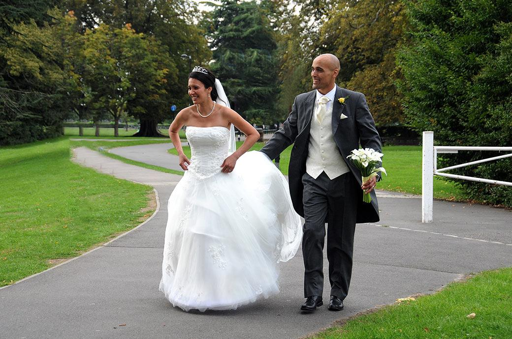 Smiling Bride and Groom taking a break from the Carew Manor wedding reception and enjoying a romantic stroll through Beddington Park Surrey