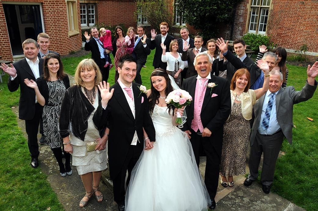 All the wedding guests waving for a group photo in the Carew Manor quadrangle at this historical Surrey wedding venue