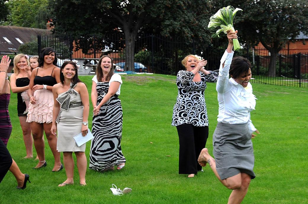 Celebrating as she catches the Bride's bouquet captured at Surrey wedding venue Carew Manor in the playing field opposite the Great Hall