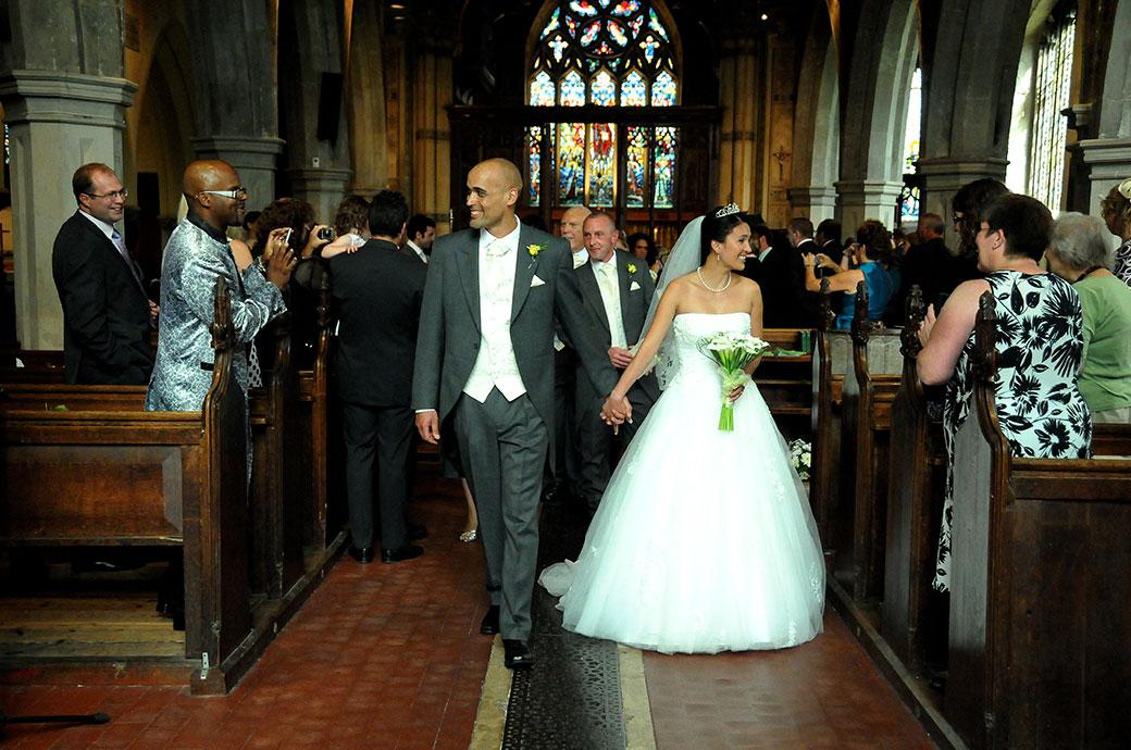 Beaming Bride and groom walk down the aisle of St Mary's Church as husband and wife now on their way to Surrey wedding venue Carew Manor next door for the wedding reception