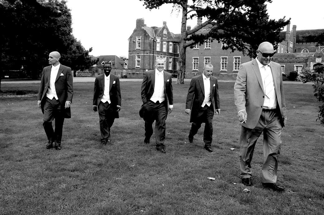 Groom and his best men walk nonchalantly walking across the front lawn of Surrey wedding venue Carew Manor on their way to St Mary's Church next door
