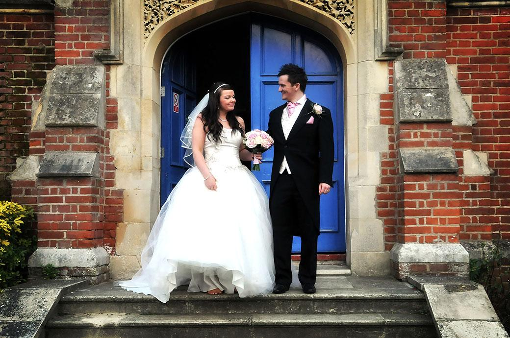 Happy Bride and Groom on the steps to the entrance of the Surrey wedding venue Carew Manor in Beddington ready to go for a romantic walk away from the celebrations