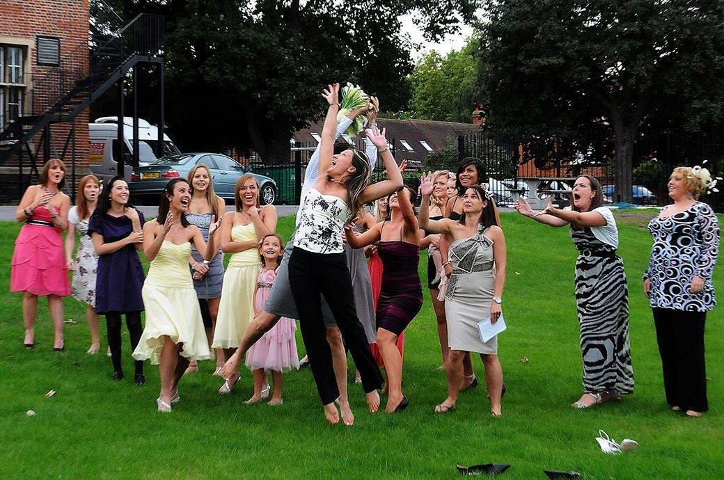 Outstretched arms and laughter captured on the lawn at Surrey wedding venue Carew Manor in Beddington as they ladies leap for the Bride's wedding bouquet