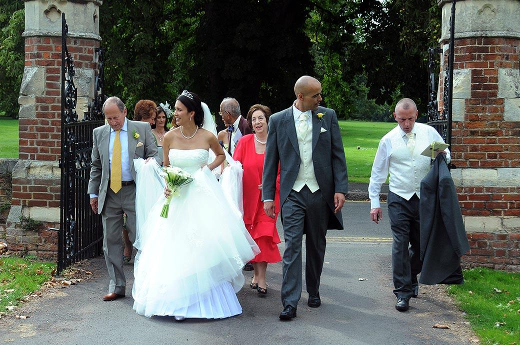 Bride and groom with family and guests walk through the main gates of wedding venue Carew Manor in Beddington Surrey after leaving St Mary's Church just next door