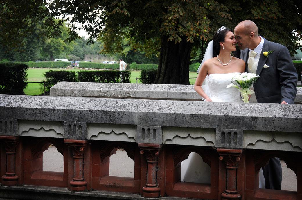 A romantic kiss on the bridge by the Bride and Groom taking a break from the reception at Carew Manor a Surrey wedding venue with an ancient history