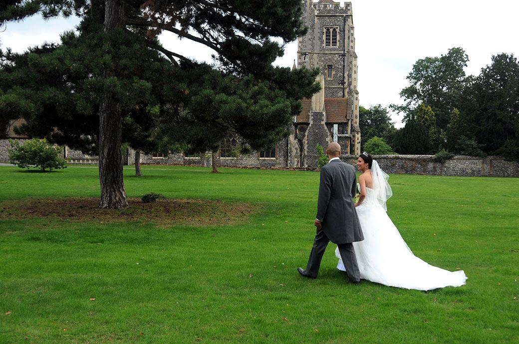 Bride and groom romantically walking across the lawn at Surrey wedding venue Carew Manor adjacent to St Mary's Church in Beddington where they were married