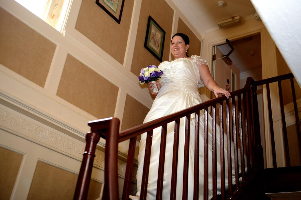 A slightly nervous but smiling Bride descends the stairs at the intimate Surrey wedding venue Chalk Lane Hotel ready for her marriage captured in this sweet wedding photo