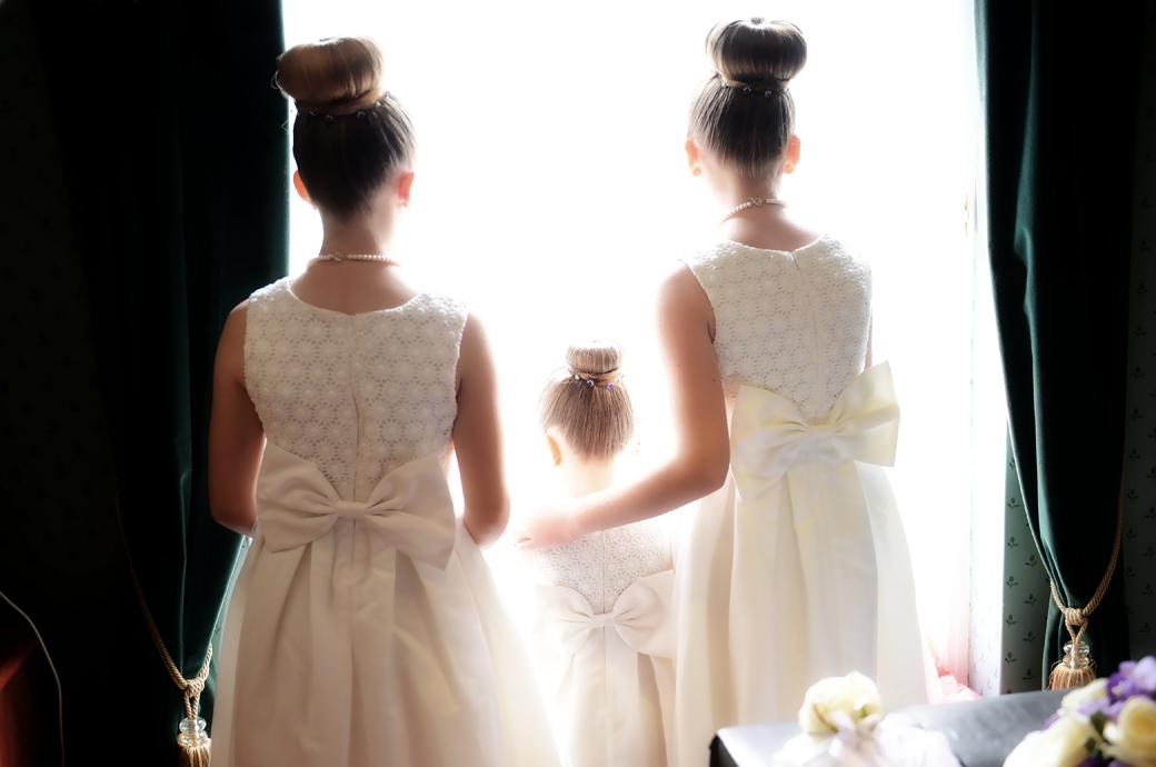 Three bridesmaids with their hair up in buns looking into the sun at the window in this wedding picture taken at Surrey wedding venue at the comfortable and relaxed Chalk Lane Hotel