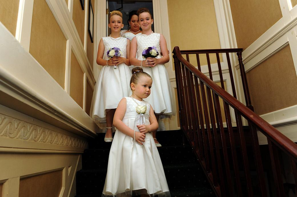 Cute bridesmaids lead the way down the stairs from the bedroom to the bridal room in this wedding photograph captured at Chalk Lane Hotel a cosy and intimate Surrey wedding venue