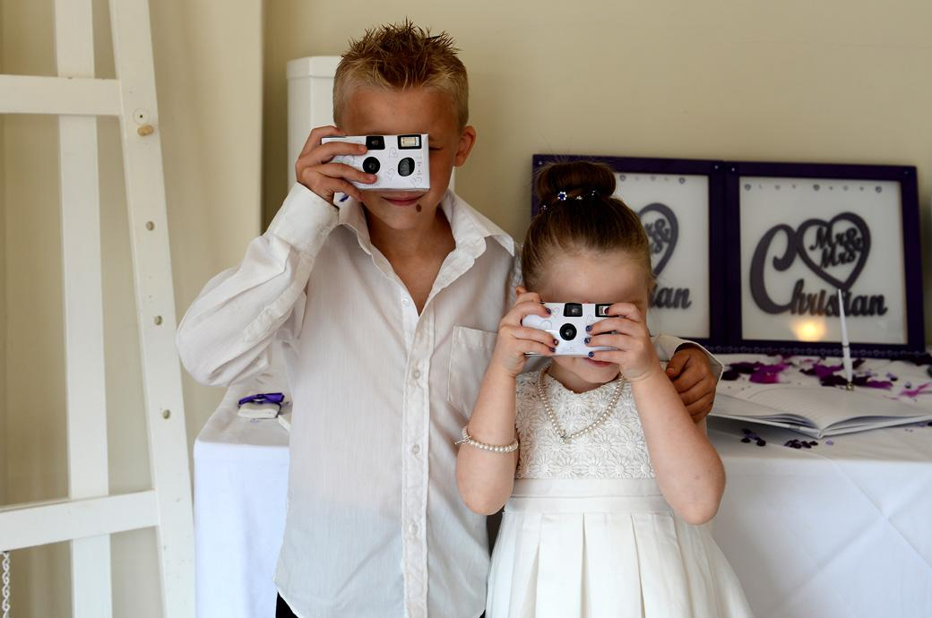 Cute bridesmaid and her brother turn their disposable cameras onto the Surrey Lane wedding photographer in this fun Chalk Lane Hotel wedding photo