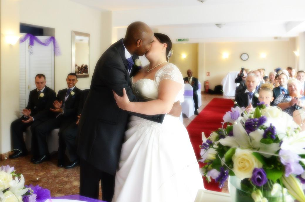 Passionate newly-weds kiss after being announced husband and wife captured in this wedding photo taken at Surrey wedding venue Chalk Lane Hotel to much applause