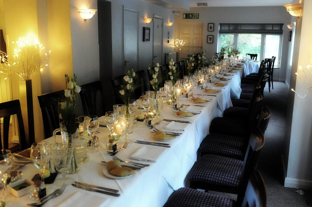 The long dining table dressed for the wedding breakfast in the hidden away Surrey wedding venue Chalk Lane Hotel in Epsom and captured by Surrey Lane wedding photography