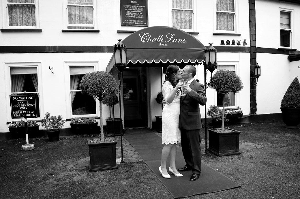 Bride and Groom standing on the red carpet captured in this wedding photograph outside the charming Surrey wedding venue Chalk Lane Hotel kissing with a champagne in hand