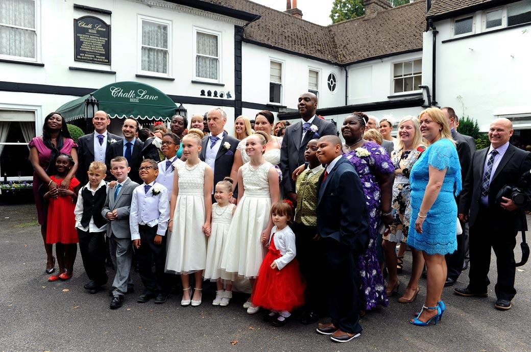 Everyone loooks towards the wedding photographer for the large group shot in this wedding photograph taken outside the intimate Surrey wedding venue Chalk Lane Hotel