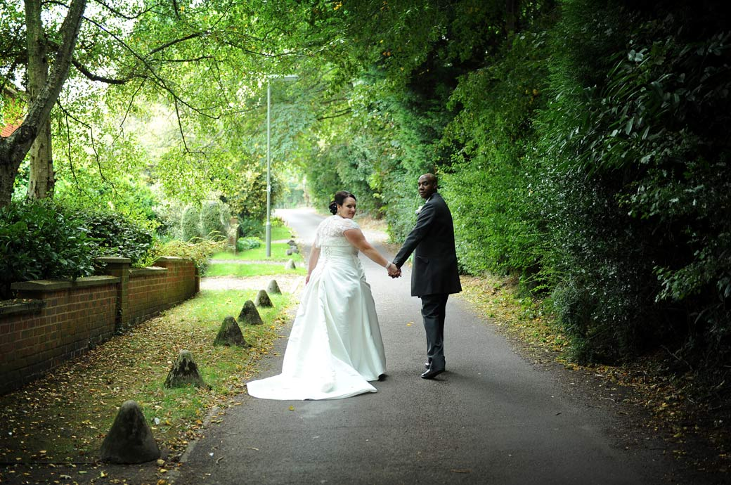 A quick glance back to the wedding photographer as the newly-weds walk down the lane from the Chalk Lane Hotel captured in this relaxed and informal wedding photograph