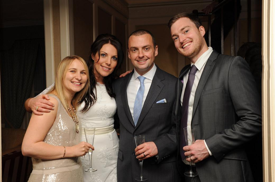 Relaxed Bride and Groom posing with friends in this informal wedding photo taken by a Surrey lane wedding photographer at the discete and hidden away Chalk Lane Hotel Epsom
