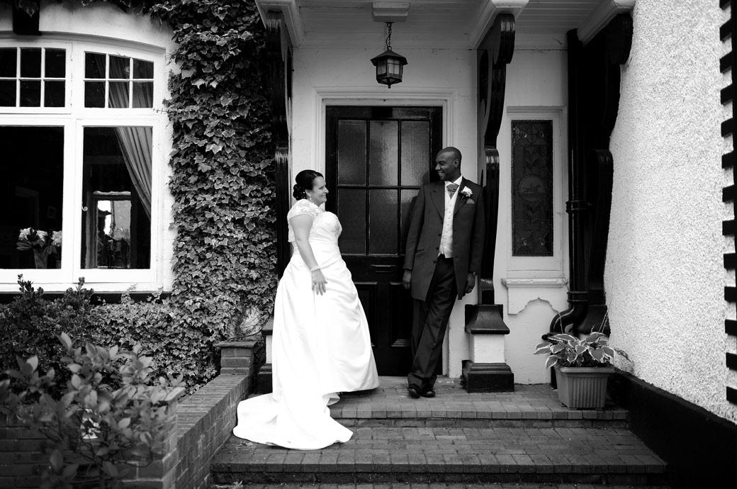 Standing in one of the doorways at the Chalk Lane Hotel in Epsom a wedding photo of the newly-weds as they smile and play around for the Surrey Lane wedding photographers