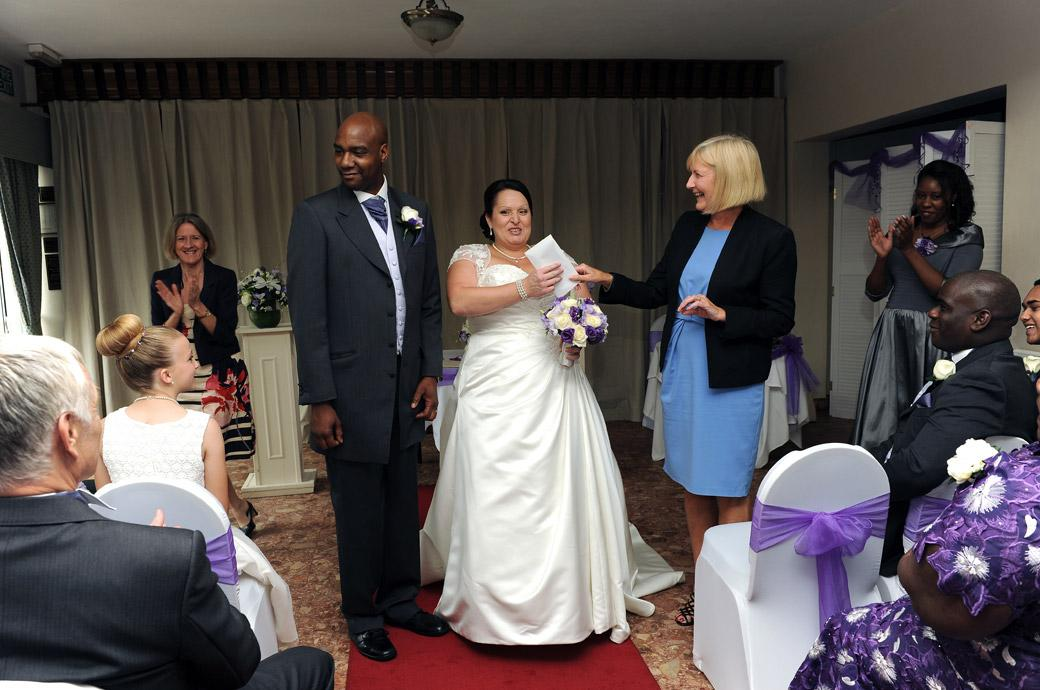 Jubliant happy Bride is presented with her marriage certificate in this wedding photograph captured at the Surrey wedding venue Chalk Lane Hotel in Epsom