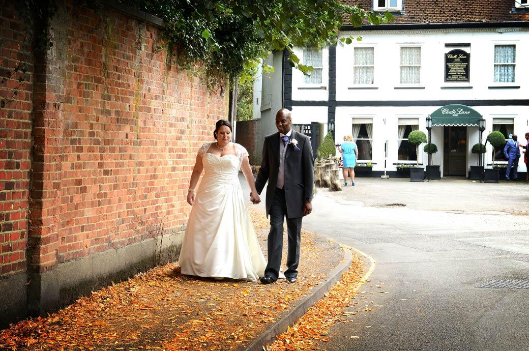 The Bride and Groom walk hand in hand down the leaf covered path leading from the Surrey wedding venue Chalk Lane Hotel in this reflective and romantic wedding picture