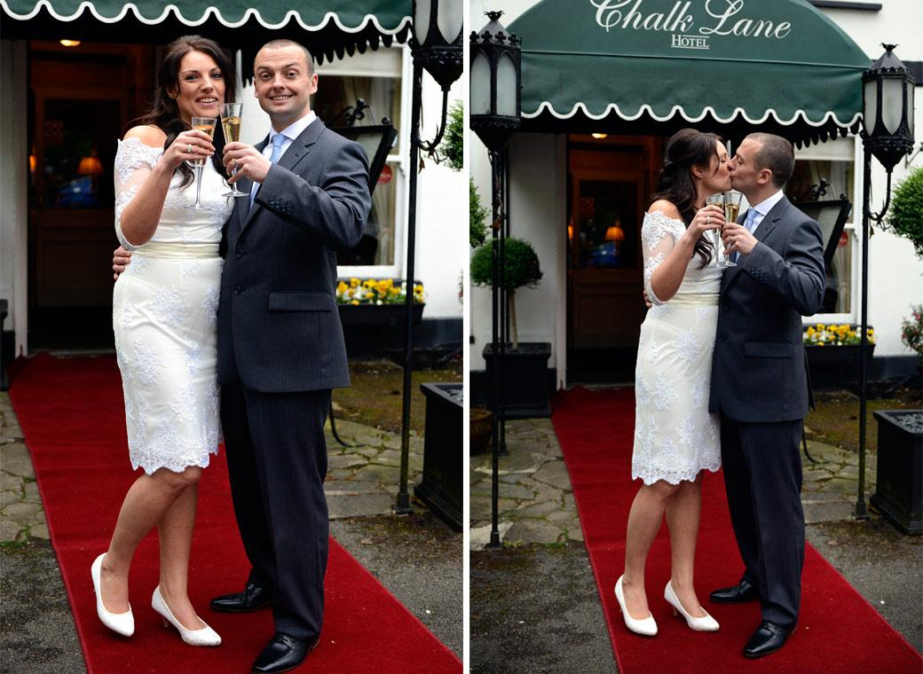 Bride and Groom having champagne and a kiss in these fun wedding pictures taken on the red carpet outside the hidden away Chalk Lane Hotel by Surrey Lane wedding photographers